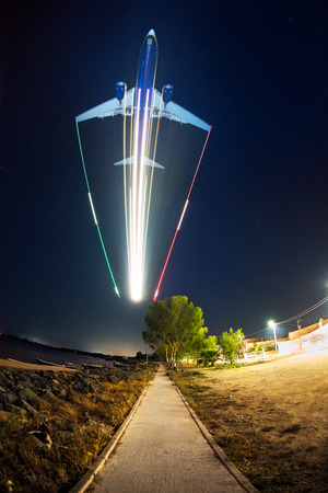trails of lights: Jet plane with lights trails landing Stock Photo