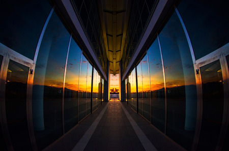 Sunset reflected on a modern glass building with perfect specular simmetry - vertical shoot