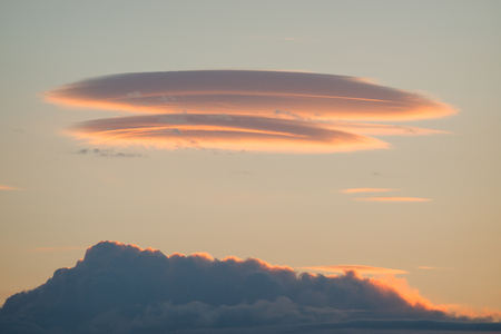Lenticular cloud over a cumulonimbus at sunrise