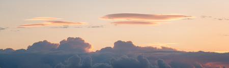 lenticular cloud: Lenticular cloud over a cumulonimbus at sunrise