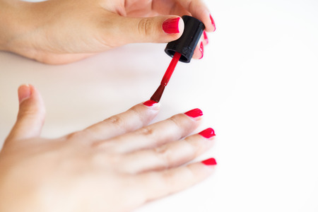 french manicure sexy woman: A close up of a female hand painting her nails red over white background
