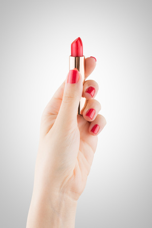 Woman hand  with red nails holds a bright red lipstick on an isolated background - vertical Stock Photo