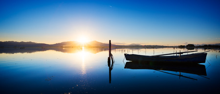 Perfectly specular reflection on the calm pond at dawn with a fisherman boat - clear blue sky with sun warm light Stock Photo