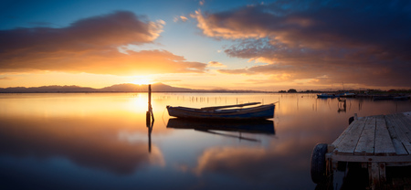 specular: Colorful sunset at the pond with specular reflection - long exposure to move the clouds and the boat, very smooth effect Stock Photo