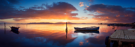 specular: Colorful sunset at the pond with specular reflection with moored fisherman boat Stock Photo