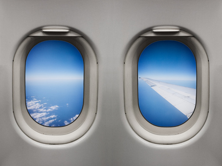 Wing view over the sea inflight from inside an airplane windows Stock Photo