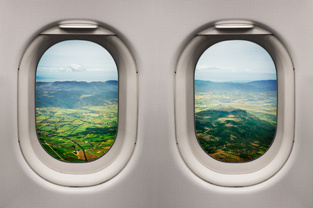 Sardinia countryside with the sea in the distance viewed from inside an airplane windows climbing after take off
