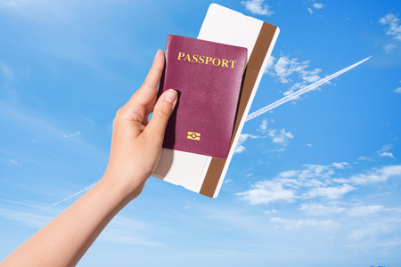 Hand holding passport and flight ticket up in the sky with a flying airplane in backgroud - airplane passport flight travel traveller fly travelling citizenship air concept