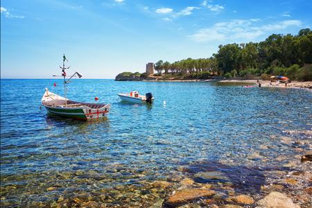 Santa Margherita di Pula - Cala dOstia, crystal clear sea on the bay with a fishing boat. Stock Photo