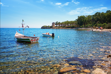 Santa Margherita di Pula - Cala d'Ostia, crystal clear sea on the bay with a fishing boat. Stockfoto