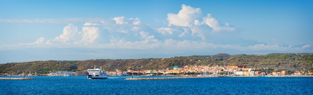 Panoramic view of Carloforte with tipical ferry ship leaving the harbor, famous place for the salt pans and tuna processing. San Pietro Island, Sardinia, Italy. Stock Photo