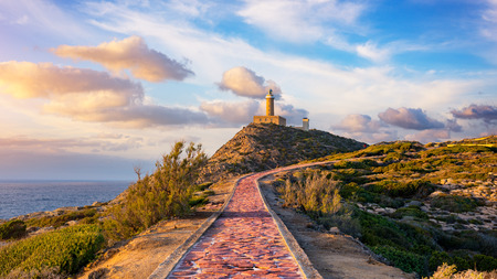 Country road in perspective leading to the lighthouse at sunset. - Isola di Pietro , Capo Sandalo Lighthouse
