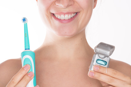 Young beautiful woman with a nice smile holding together an electric toothbrush and dental floss, isolated over a white background