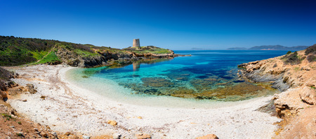 Panoramic view of Piscinni' ( Teulada Sardinia) bay with calm and turquoise sea, and on background the famous coastal tower of Piscinni'. Stockfoto