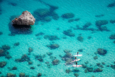 Aerial view of people padding on SUP (stand up paddle) on crystal clear blue sea with rocks under water. Unidentifiable people paddle boarding. 스톡 콘텐츠
