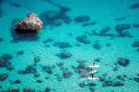 Vue aérienne de personnes rembourrage sur SUP (stand up paddle) sur une mer bleue cristalline avec des rochers sous l'eau. Embarquement de personnes non identifiables. Banque d'images - 107085286
