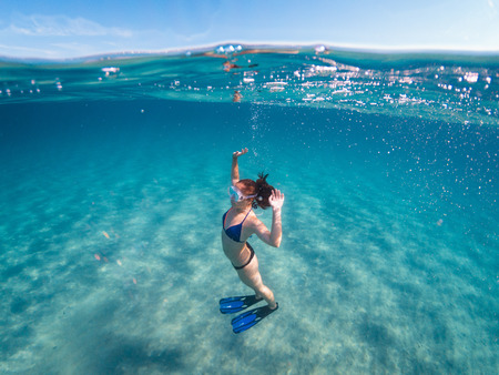 Girl with mask and fins underwater in apnea, half underwater photography