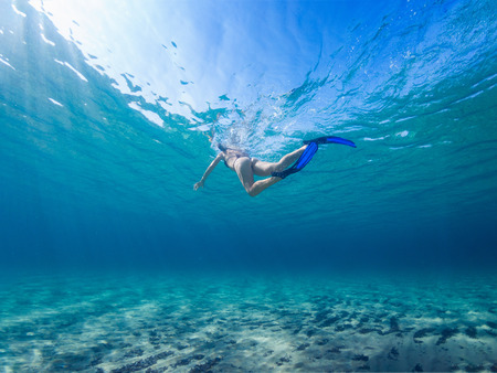 Girl snorkeling on a clean turquoise sea