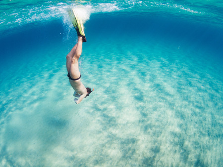 Young man performing an immersion in the turquoise sea. Man diving on the sea