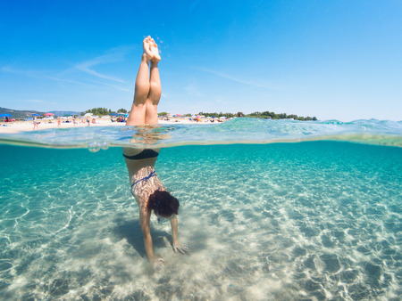 Young girl doing the vertical half underwater on a turquoise sea . Half underwater photography.