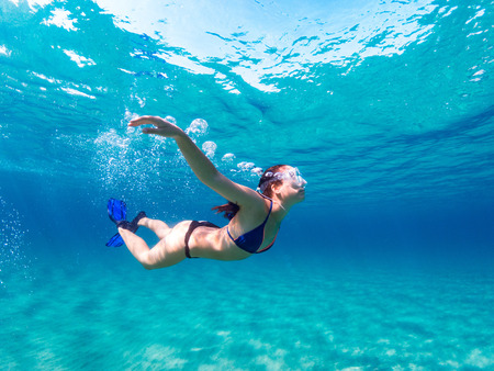 Young girl with mask and fins diving undewater on a clean blue sea. 免版税图像