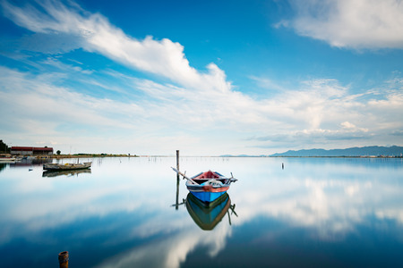 Fisherman boat on the calm lagoon with perfect water reflection of the cloudy sky - long exposure to move the boat the sea and the clouds Stockfoto - 116137577