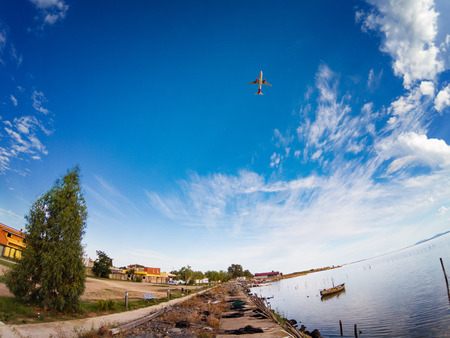 Fisherman lagoon in a calm day with an airplane in take off on the sky. Wooden pier boat at the river.