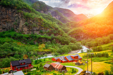 Very small village on the shore of a river in Norway at sunset Imagens