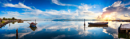 Panoramic view of calm lagoon at sunset with typical fisherman boats and perfect water reflections Stockfoto - 116138343