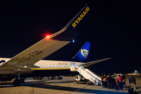 Bergamo, Italy 07102018 -  Ryanair B737-800 boarding passengers at nigh, flight from Bergamo to Cagliari. Ryanair winglet close up with rear entrance.