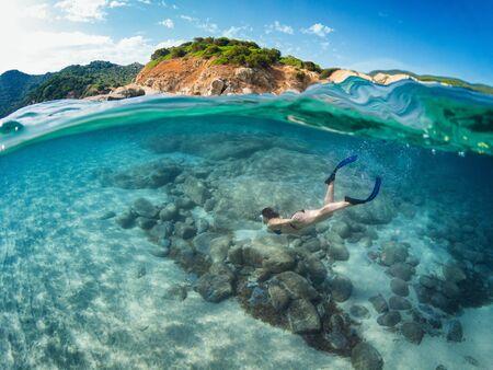 Half underwater with girl diving on a beautiful clear south Sardinia sea. Sardinia, Costa Rei - Cala Sinzias