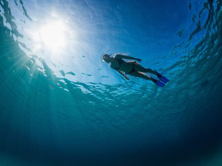 Young girl viewed from the bottom of the sea snorkeling on a turquoise sea.