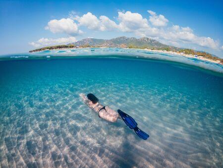 Young beautiful girl diving underwater, on turquoise Sardinia sea. Half underwater photohraphy. Reklamní fotografie - 132089720