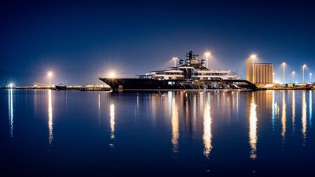 Luxury mega yacht moored in the harbor at night with calm sea reflections.