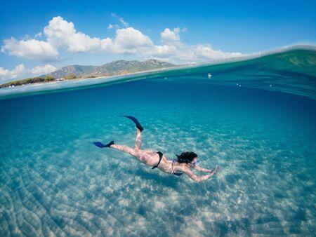 Hermosa joven buceando bajo el agua, en el mar turquesa de Cerdeña. Fotofrafia semi submarina.