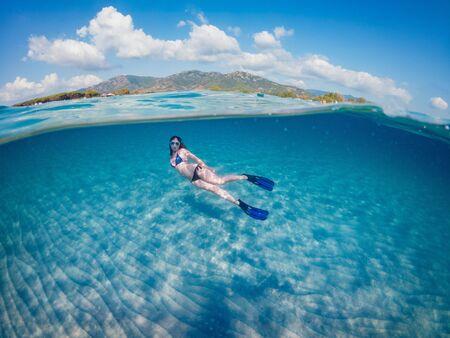 Young beautiful girl diving underwater, on turquoise Sardinia sea. Half underwater photohraphy. Reklamní fotografie