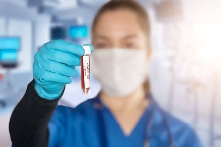 Coronavirus covid 19 infected blood vial in hand of female doctor with surgical mask and glows. Coronavirus covid 19 reseach laboratory, coronavirus covid-19 vaccine research. Foto de archivo