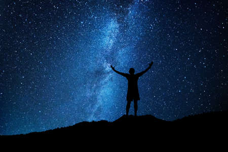 Man who feels on top of the world looking at the milky way. Man silhouette looking at the milky way.