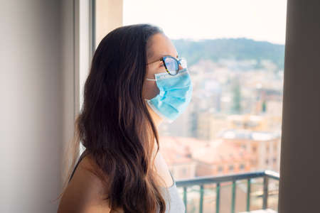 Woman wearing surgical mask in isolation at home for virus outbreak or hypochondria, looking out her window. Woman wants freedom, denied by pandemic isolation.