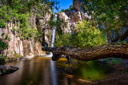Small and idyllic waterfall in the mountains covered with surrounding trees. Cagliari, Maracalagonis waterfall called