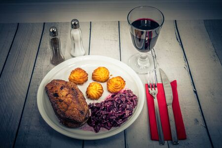 Fried duck with red cabbage and croquettes