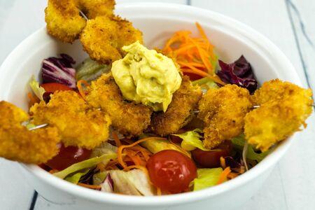 Crispy wrapped and fried Shrimp on a shashlik stick with salad Stock Photo