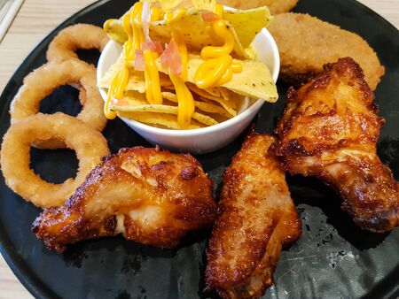 Chicken wings with onion rings and chips