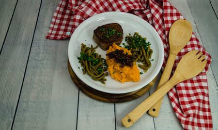 Grilled beef fillet steak with spices beans and mashed sweet potatoes Фото со стока