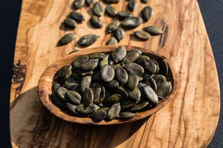 roasted pumpkin seeds on olive wood Foto de archivo