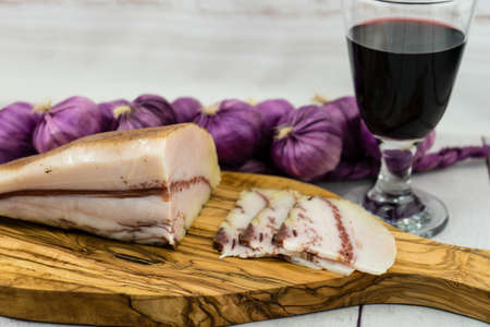 A piece of ham on olivewood with a glass of redwine