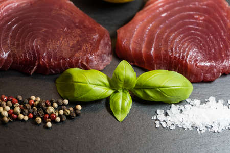 two raw tuna steaks and spices