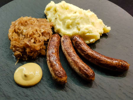 Traditional German food Sausages from Nuernberg with sauerkraut and mashed potatoes