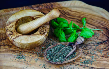 Fresh and rubbed basil on olive wood