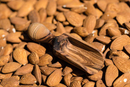 a pile of almonds and a glass with almond oil